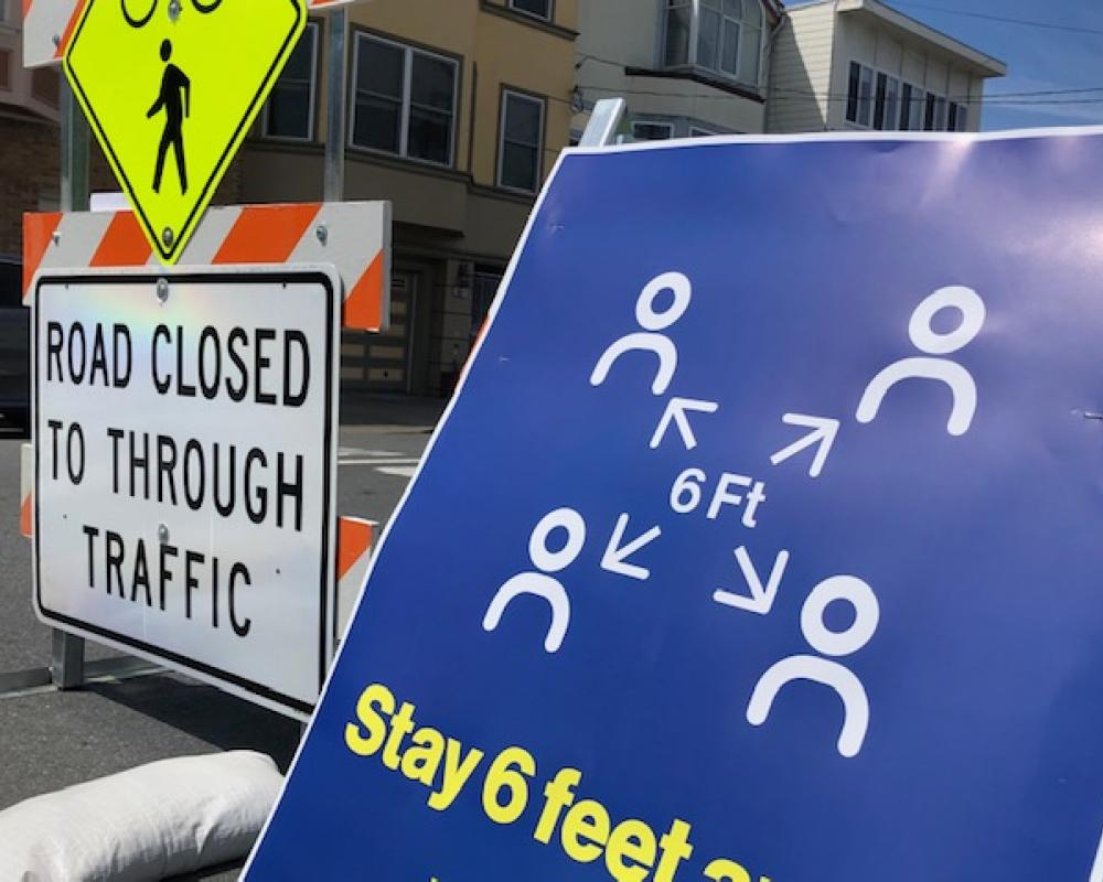 Slow Street barricade and social distancing sign