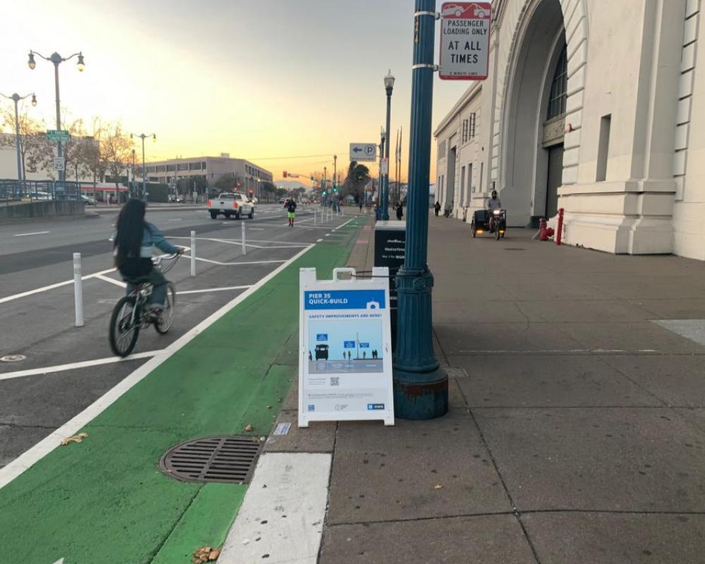 person riding bike on green bike path past Ferry Building and Quick Build sandwitch board