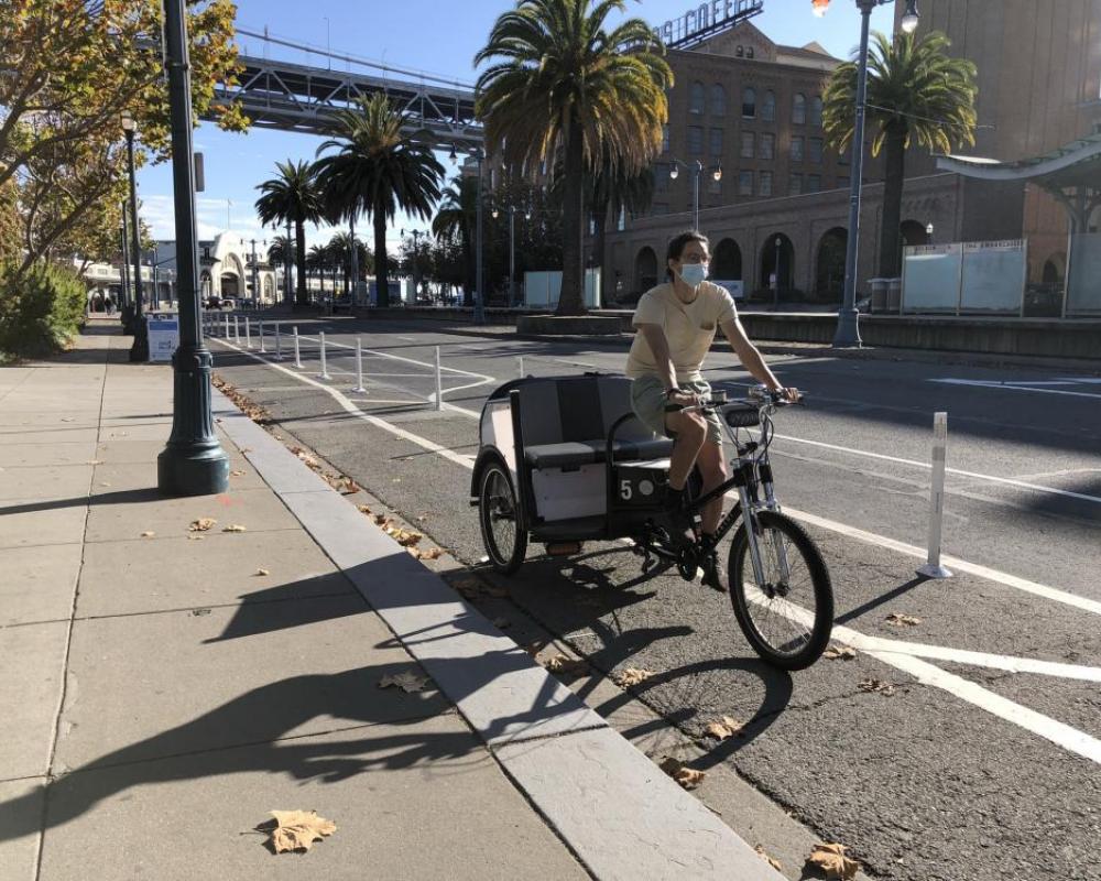 person riding a pedicab along the Embarcadero