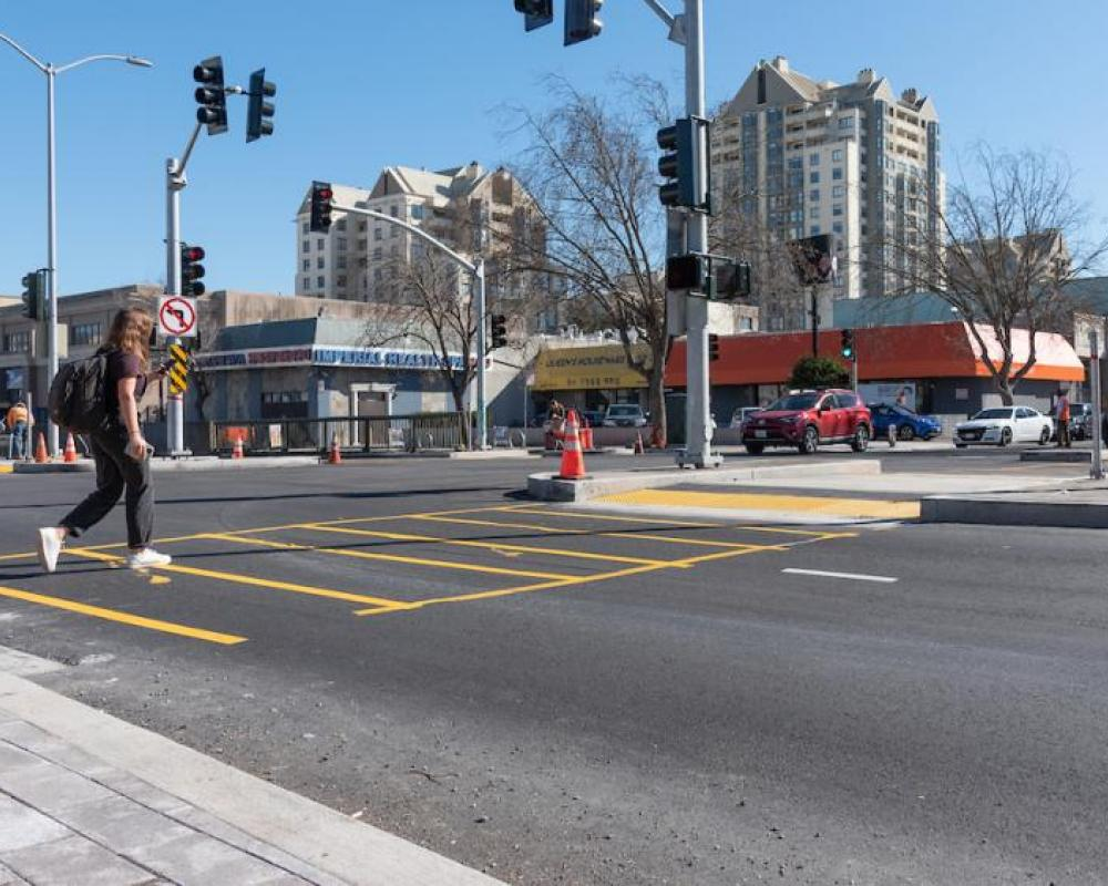 Image of person crossing the new surface-level crosswalk at Steiner