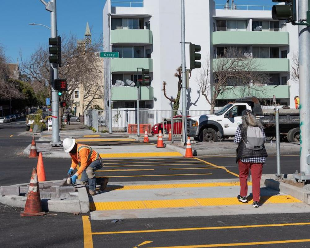 A worker installs decorative pavers at a new median refuge while a woman crosses Geary and Steiner.