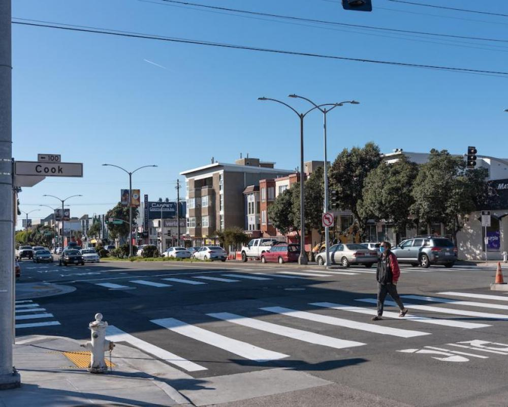 Image of woman crossing at a new crosswalk at Cook Street