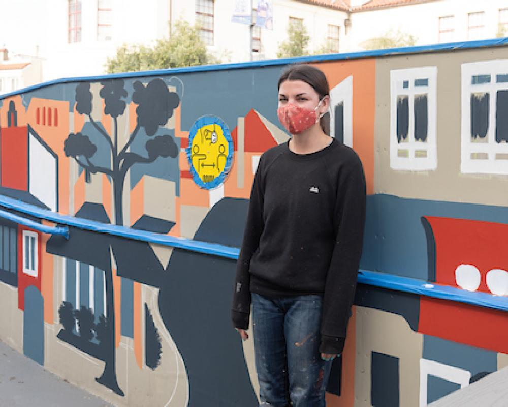 "Artist Emily Fromm with her mural ""East West Portal"""