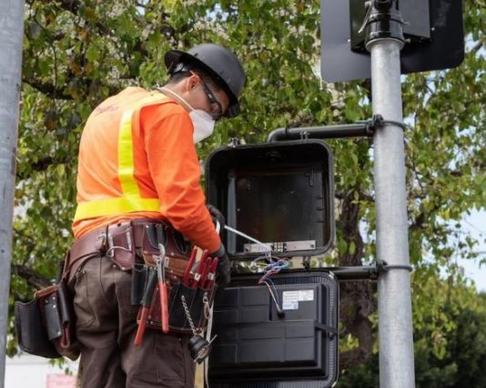 Photo of A crew member programming a pedestrian signal on a recently-installed traffic signal on Van Ness.