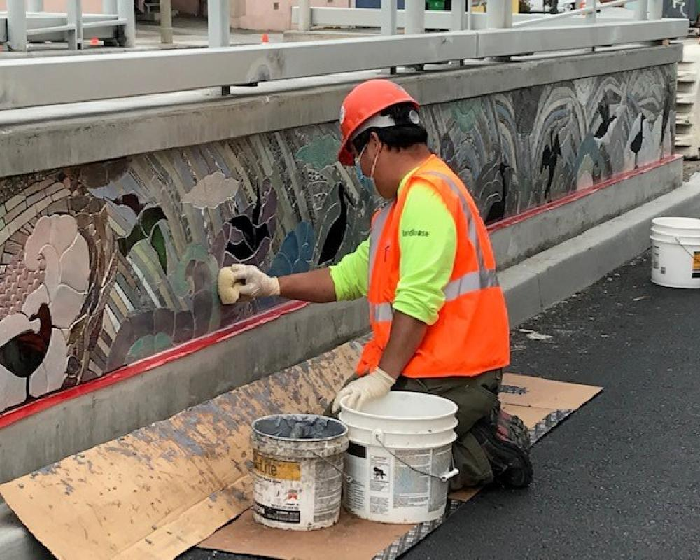 Photo of A worker installing mosaic on the ADA Platform at 40th Avenue