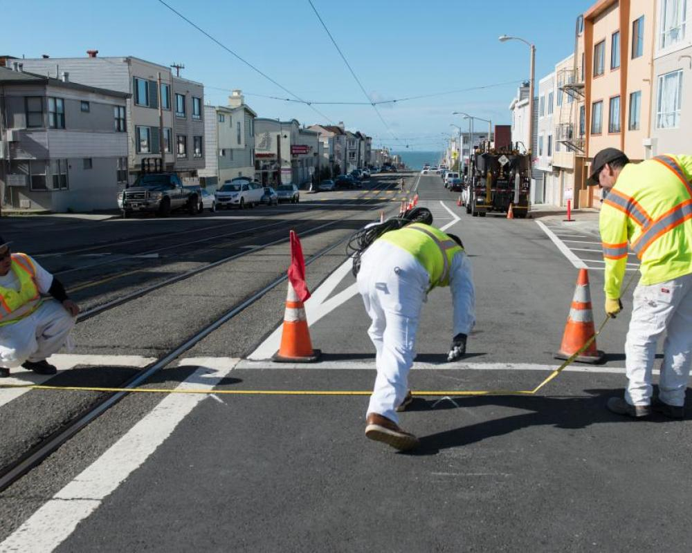 Photo of crew painting new safety striping on Taraval Street