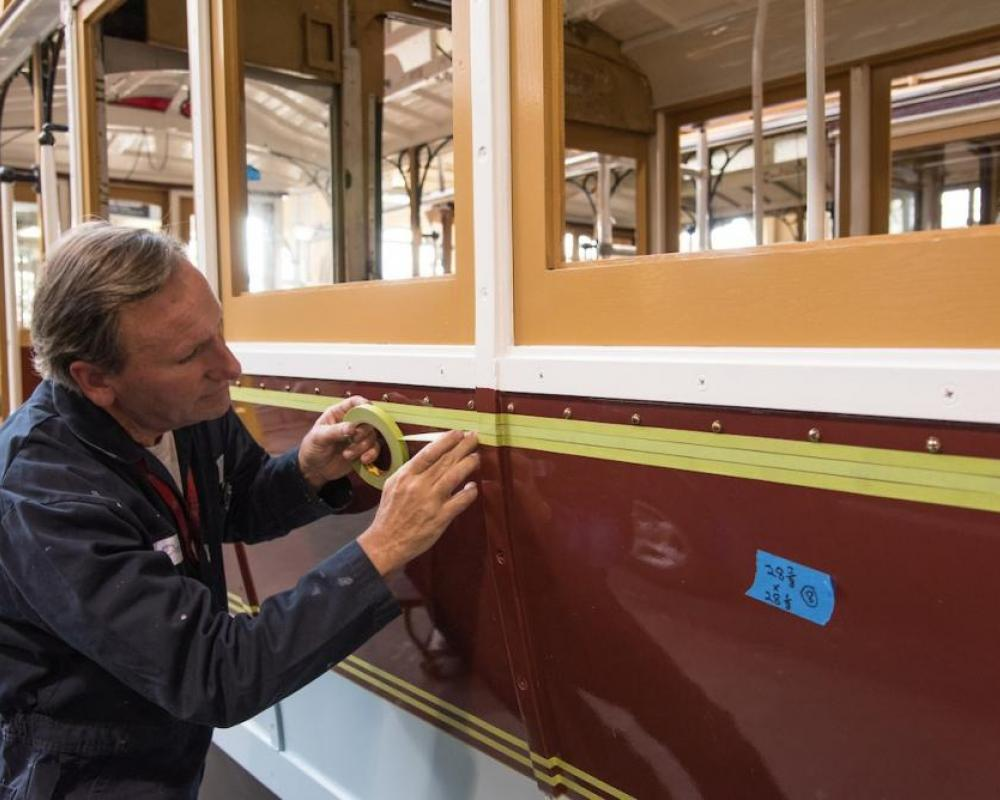 A painter lays down masking tape to paint striping on the side of Powell St. Cable Car 22,
