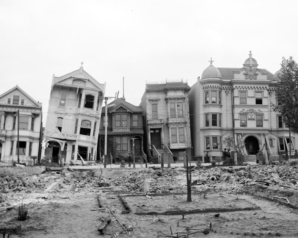 black and white photo of houses damaged and leaning after the 1906 earthquake and fire