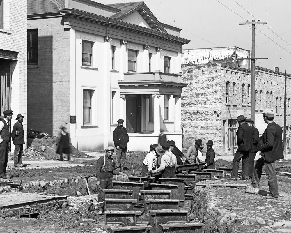 black and white photo of men working on rails in the street