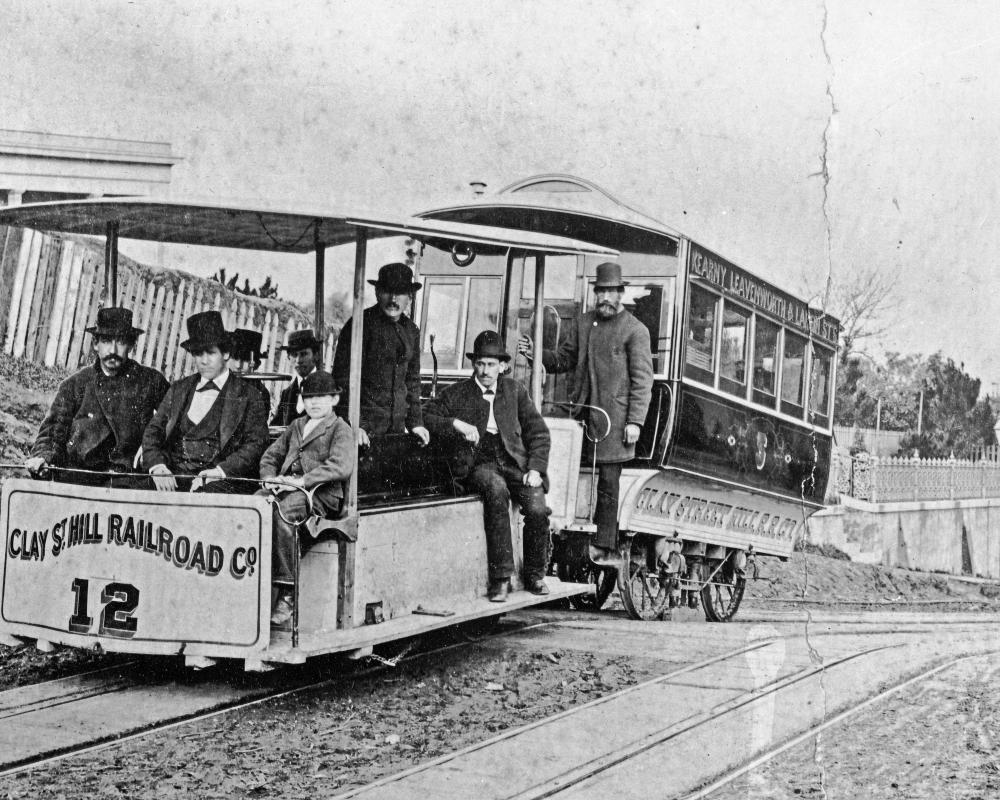 black and white photo of original cable train on clay street hill in 1873 with people on board.