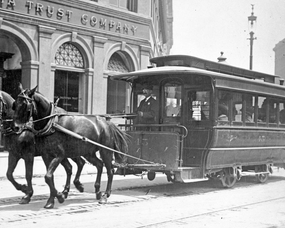 black and white photo of a horse-drawn streetcar in downtown san francisco in the late 1800s.