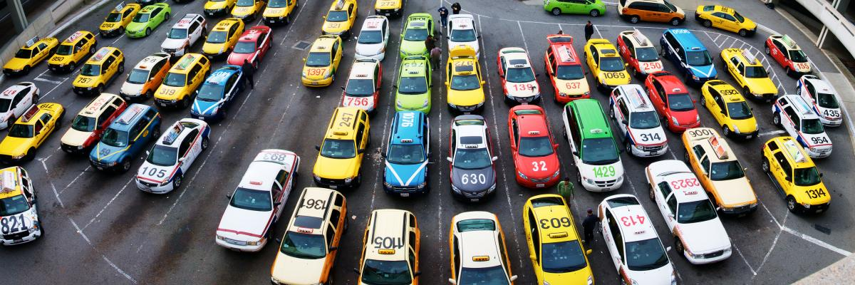 overhead view of taxi cabs in parking lot of SFO airport showing many different cars and company liveries