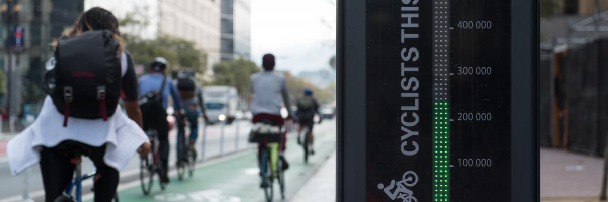Picture of people biking past Market St bike totem