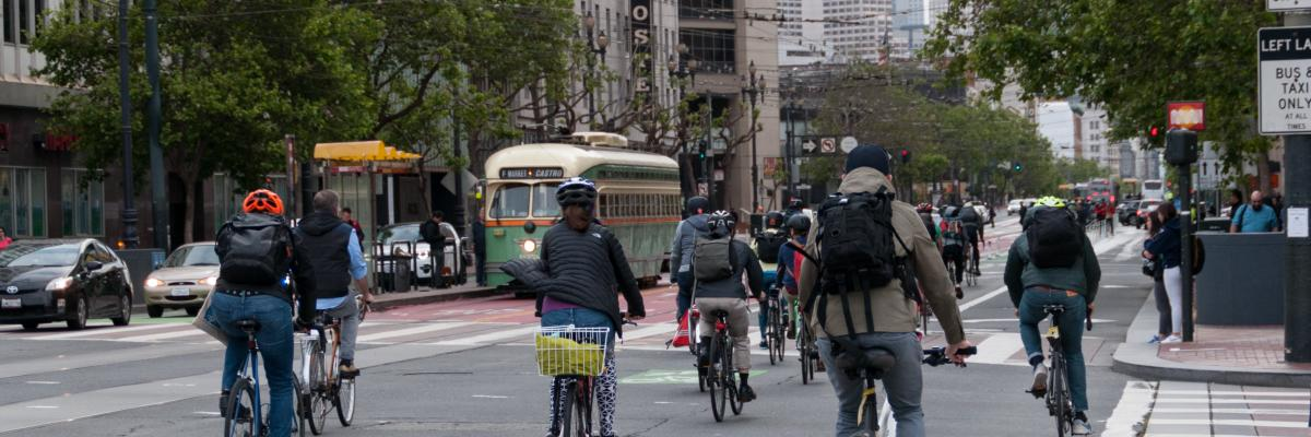Picture of people biking on Market St crossing Van Ness Ave