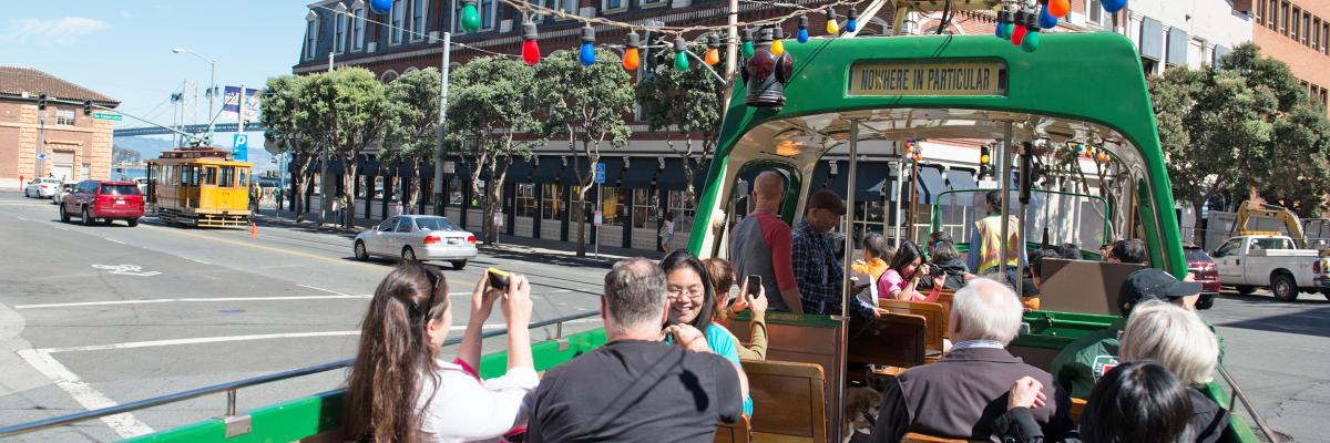 Riders on the open-topped boat style Blackpool streetcar on the Embarcadero