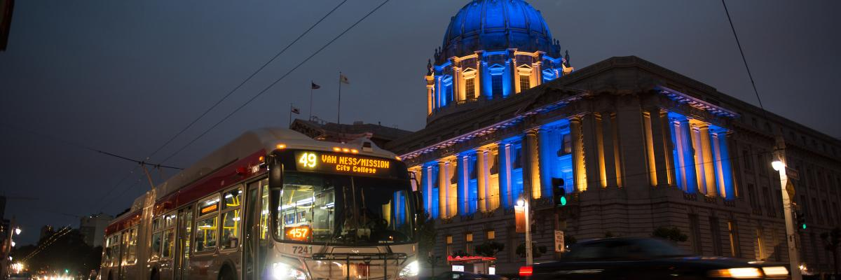 49 bus drives past City Hall with blue and yellow lights