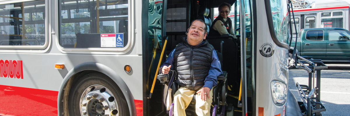 man in electric wheelchair unloading from Muni bus while smiling with smiling operator in background