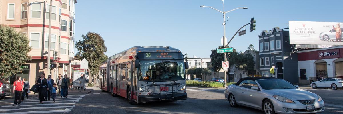 38 Bus Merging into Traffic on Geary Boulevard with pedestrians crossing sidewalk on left.