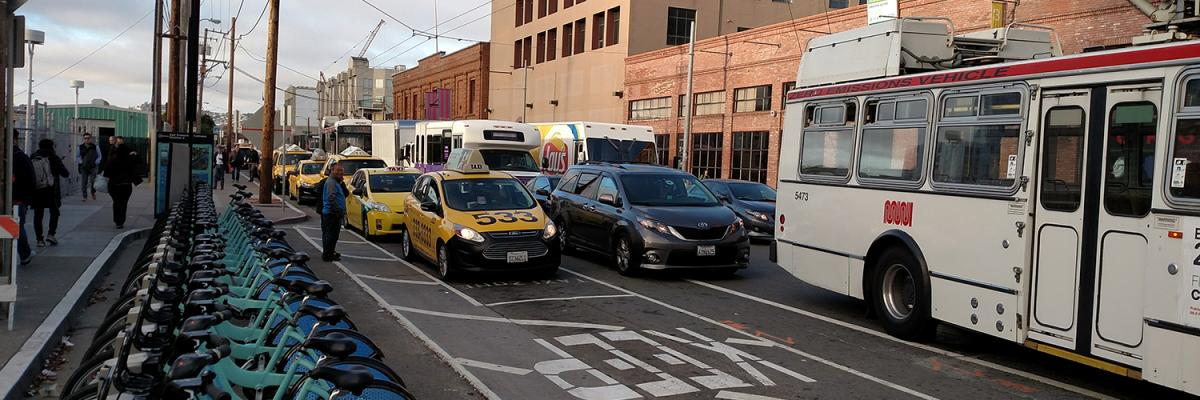 Taxis, buses, and bikes lining up at Caltrain station