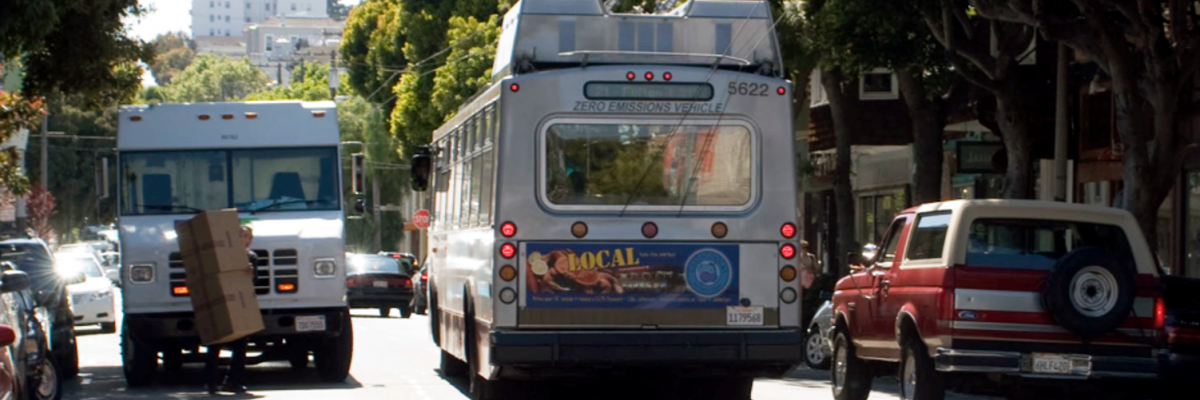 Bus weaves around double-parked vehicles on Hayes Street