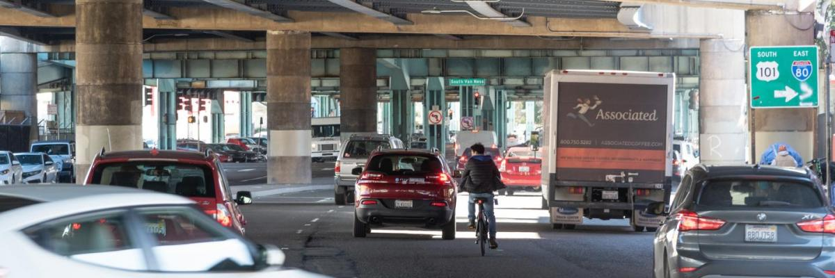 A bicyclist rides in mixed traffic on 13th Street