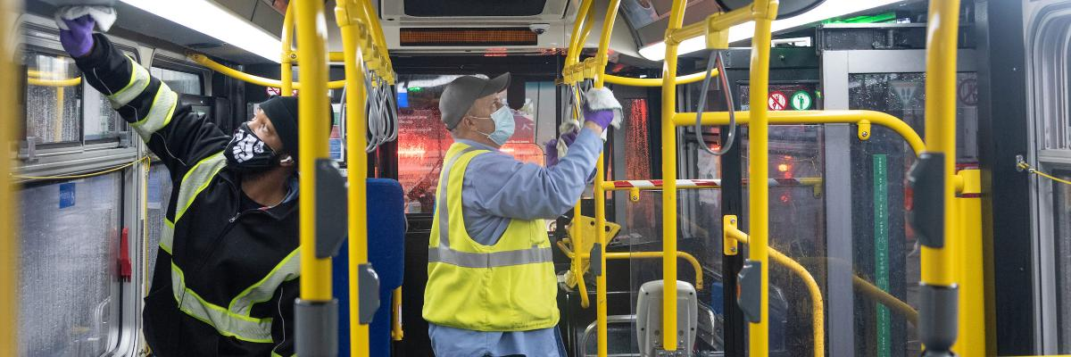 Car cleaners wearing masks and disinfecting a bus