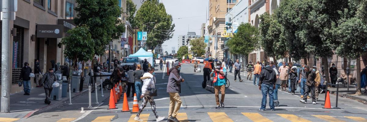 People walking across a crosswalk in the Tenderloin