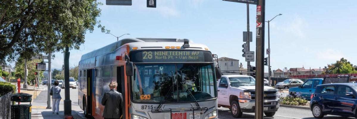 people boarding 28 19th avenue bus at bus stop