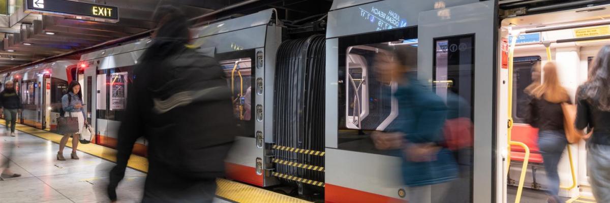 People walking past a train at Embarcadero Station