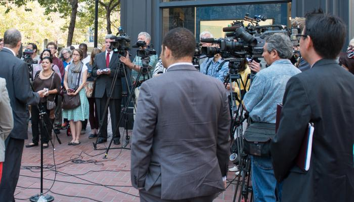 group of news camera people at press event on market street
