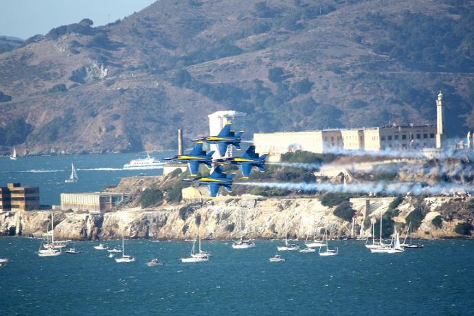 Blue Angels fighter jets in tight formation flying passed Alcatraz Island during the day.
