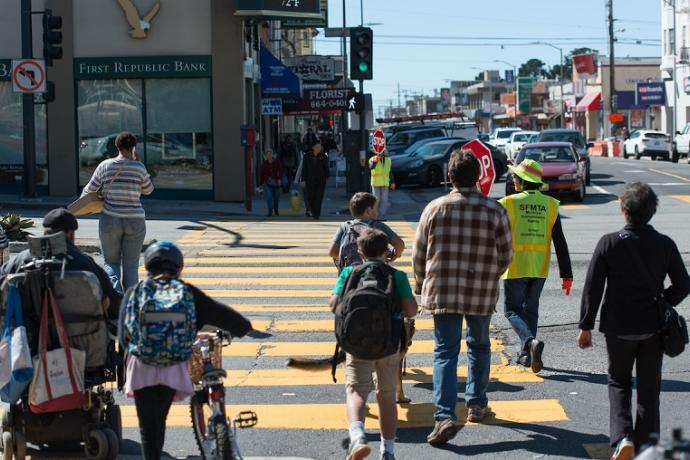 Children and adults cross a street, including a crossing guard and a girl walking a bicycle.