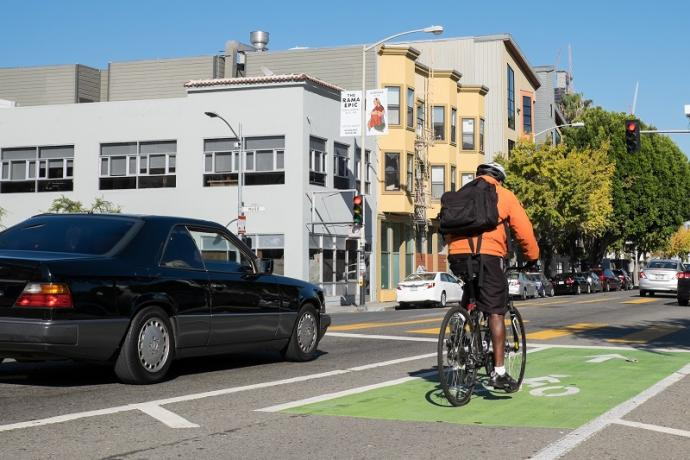 And man on bike and car traffic travel on Folsom Street at Russ Street.