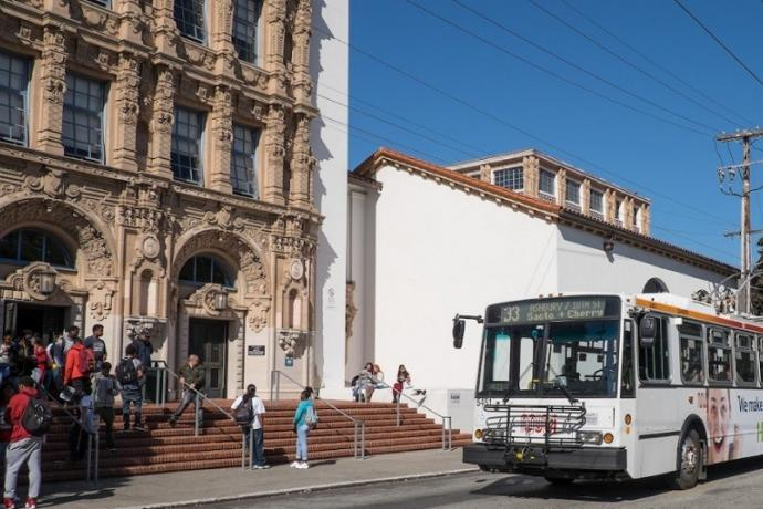 White and orange Muni trolley bus sits in front of Mission High School while students mingle on the front steps.