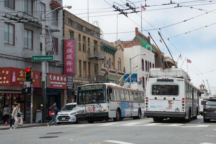 Two Muni coaches passing each other as people use a crosswalk in Chinatown during the day.
