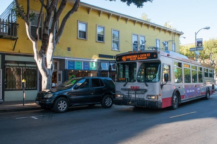 Outbound 48 Quintara-24th Street bus driving past a yellow building in the afternoon.