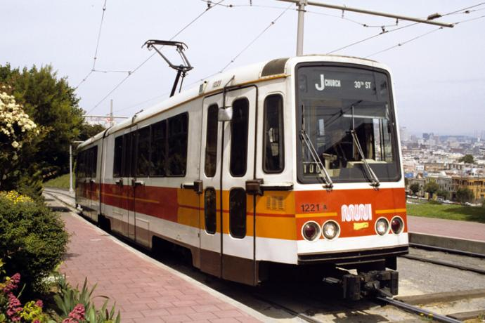 Muni Boeing LRV at outbound stop at top of hill in dolores park in the 1980s with a view of the city skyline behind it