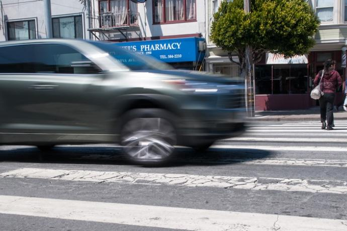 A car appears blurry as it moves through a crosswalk in a San Francisco intersection with pedestrians crossing in the background on Geneva Avenue.