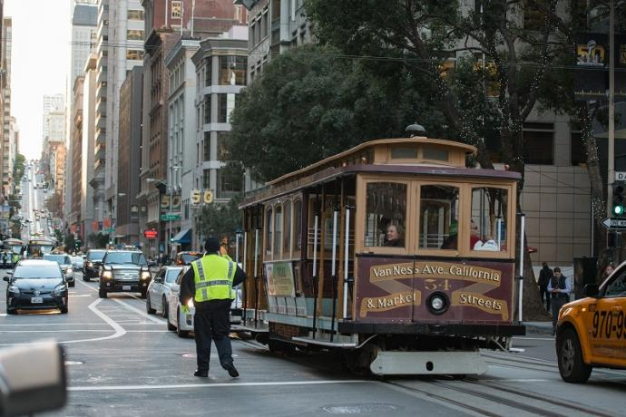 California Cable Car being guided by a parking control officer in traffic.