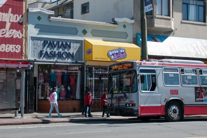 A 14 Mission Muni trolley bus stopped in front of local shops in the Excelsior district.