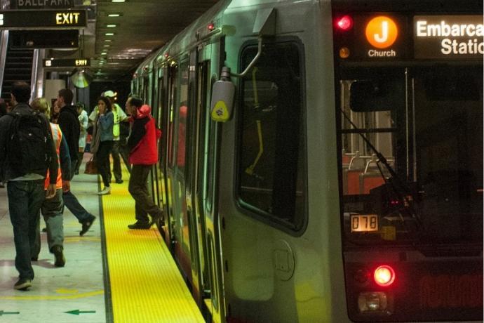 People disembark from a J Church Muni Metro train at Embarcadero Station.