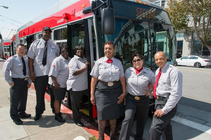 Muni operators pose in their new uniforms in front of a parked Muni bus.