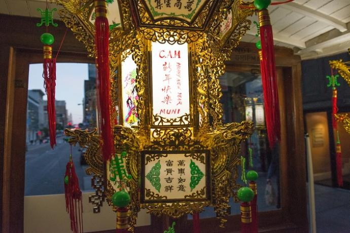 "Photo of a Chinese lantern with ""CAM,"" ""Happy New Year"" and ""Muni"" written in English next to Chinese characters, on the inside of a motorized cable car."