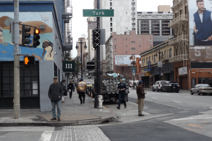 """Pedestrians cross downtown streets with the """"Turk"""" street sign above them."""