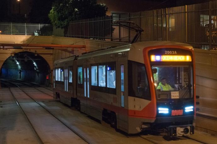 """A new Muni train displaying a sign that says """"Test Train"""" on the tracks just outside the Sunset Tunnel at night."""