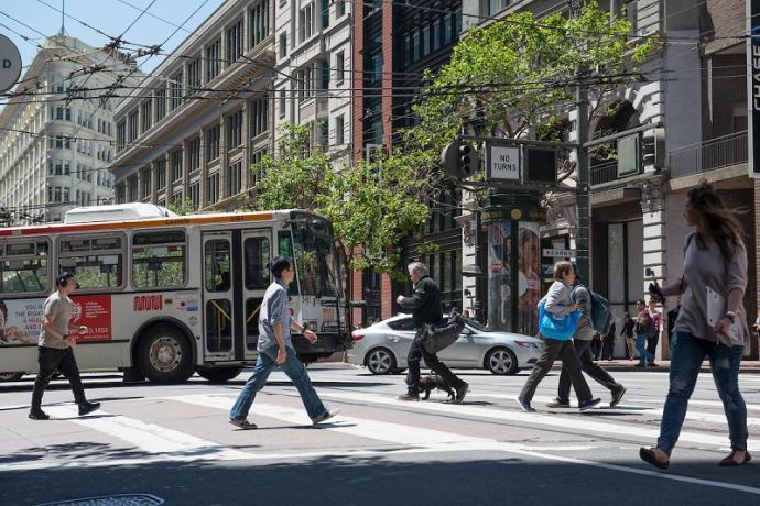 Pedestrians cross a downtown street as a Muni bus and cars cross behind them.