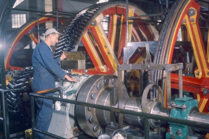 Color photo of a man standing next to the huge pulleys of the cable winding machinery, looking into a bronze oil box on top of a large bearing housing.