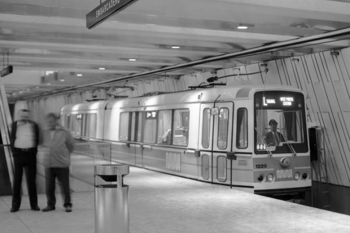 Black and white photo showing a Boeing LRV stopped at an empty platform in Embarcadero Muni Metro Station.