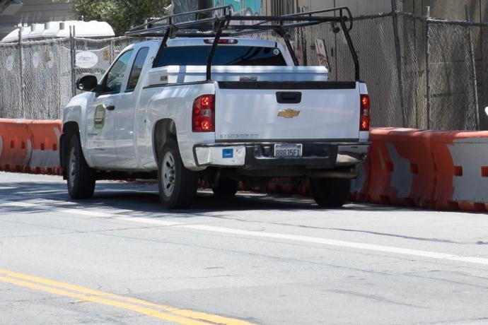 white pickup truck parked outside construction zone with contractor parking permit sticker on bumper