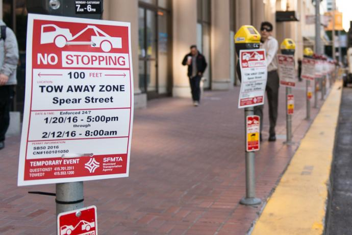 row of parking meters with no stopping temporary event signs